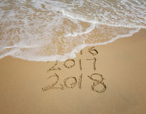 inscripción 2018 y 2017 escrita en la arena mojada de la playa Foto de archivo