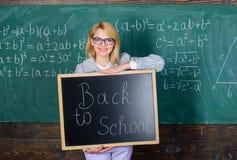Inscripci?n de la pizarra del control de la mujer del profesor de nuevo a escuela Es tiempo de la escuela otra vez Profesor de es fotografía de archivo libre de regalías