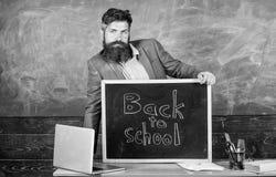 Inscripci?n de las recepciones del profesor o del educador de nuevo a escuela El educador experimentado del profesor acoge con sa foto de archivo