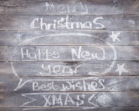 Inscripciones de la tiza del Año Nuevo de la Navidad en el fondo de madera Foto de archivo libre de regalías