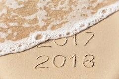 2017 2018 inscripciones escritas en la arena amarilla mojada de la playa que es Imagen de archivo