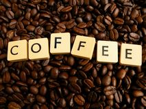 Inscript coffee written on cubes on coffei beans. Inscript coffee made by letters written on cubes with fresh caffeic beans in background Royalty Free Stock Image