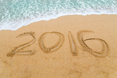 inscription 2016 écrite sur la plage sablonneuse avec l'approche de vague Images stock