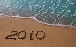inscription 2010 sur le sable près de la mer azurée Image stock