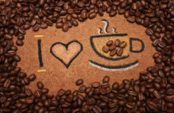 Inscription:. I love coffee written on a brown background surrounded with coffee grains Stock Images