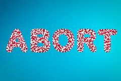 Concept of abortion medicine. Inscription abort white and red capsules on a blue background top view. concept of abortion medicine royalty free stock photography