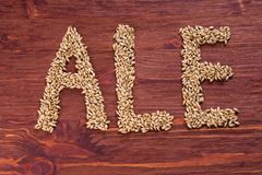 The inscription of ale by malt grains on wood background. Craft. Beer brewing from grain barley malt. Ale or lager from pale or dark pilsner malt stock photography