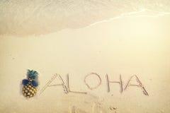 Inscription Aloha written on the sandy beach with ocean wave Royalty Free Stock Image
