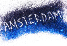 Inscription Amsterdam on black and blue glitter sparkles on white background Stock Images