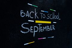 The inscription on the asphalt with white chalk back to school, colorful markers and yellow line vector illustration