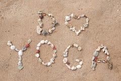 Inscription avec du yoga des textes de coquilles sur la plage Photographie stock libre de droits