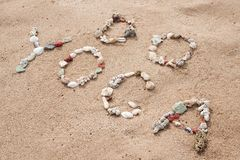 Inscription avec du yoga des textes de coquilles sur la plage Images stock