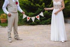 Inscription avec la date du mariage dans les mains les jeunes mariés Image libre de droits