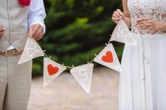 Inscription avec la date du mariage dans les mains les jeunes mariés Photos stock
