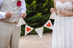Inscription avec la date du mariage dans les mains les jeunes mariés Photographie stock libre de droits