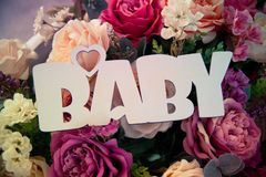 The inscription `BABY` on polyfoam against the background of a bouquet of flowers from roses royalty free stock image