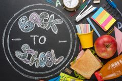 The inscription back to school, on a school board with handles, chalk, an alarm clock, and school breakfast.  stock photos