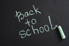 Inscription back to school on chalk blackboard. Inscription in chalk on a black chalk Board: Back to School Royalty Free Stock Images