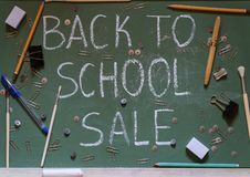 Green school board with the inscription sale surrounded by a variety of office. The inscription back to school sale on a green school blackboard with chalk royalty free stock photo