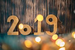The inscription 2019 on the background of New Year`s decorations on a wooden background royalty free stock photos