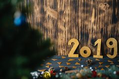 The inscription 2019 on the background of New Year`s decorations on a wooden background stock image