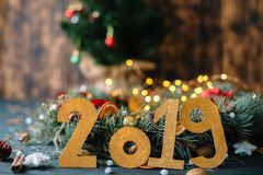 The inscription 2019 on the background of New Year`s decorations on a wooden background royalty free stock photo