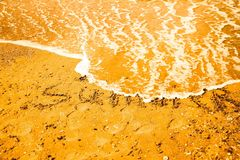 Inscription beach sand SUMMER. Concept photo of summer travel and vacation. Royalty Free Stock Image
