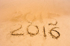 Inscription 2015 and 2016 on a beach sand, the wave is starting to cover the digits 2015 Royalty Free Stock Images