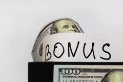 Gift package with dollars on the table on a white background, the inscription Bonus stock image