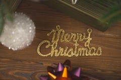 Inscription brillante d'or de Joyeux Noël sur un fond en bois rustique Image stock