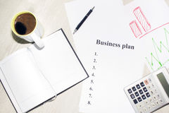 An inscription of the business plan, execution points, there is a notebook and a calculator next to it.  royalty free stock photography