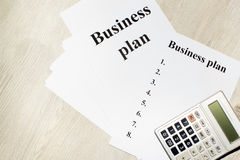 An inscription of the business plan, execution points, there is a notebook and a calculator next to it.  stock image