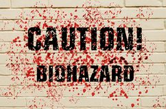 Inscription Caution Biohazard on a bloodstained brick wall. Stock Images