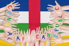 Inscription Central African Republic on the children`s hands against the background of a waving flag of the Central African. Republic stock photos