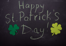 Inscription on chalkboard Happy St.Patricks Day and two leaf clover Stock Photo