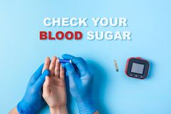 Inscription check your blood sugar, Nurse making a blood test with lancet. Man`s hand, red blood drop, Glucose meter. Inscription check your blood sugar and royalty free stock image