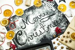 Merry Christmas. written on a black board sprinkled with flour. Christmas cooking concept Royalty Free Stock Photos
