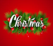 Inscription Christmas with fir branches and holly Stock Images