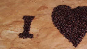 Inscription from coffee beans. Heart of coffee beans. The inscription I love coffee. In the kitchen, a marble countertop. stock footage