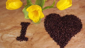 Inscription from coffee beans. Heart of coffee beans. The inscription I love coffee. On the kitchen table. With yellow tulips. stock footage