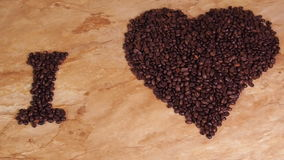 Inscription from coffee beans. Heart of coffee beans. The inscription I love coffee. On the kitchen table. stock video