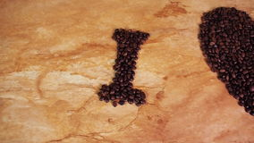 Inscription from coffee beans. Heart of coffee beans. The inscription I love coffee. On the kitchen table. With yellow tulips stock video footage
