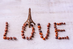 Inscription coffee beans word LOVE statue and Eiffel tower Royalty Free Stock Photo