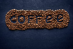 Inscription of coffee from coffee beans on the dark background Stock Photos