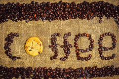 Inscription coffee with cookie as o. Text made of coffee grains on burlap with cookie as o Royalty Free Stock Image