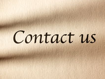 The inscription contact us on a sheet of paper. Royalty Free Stock Photo
