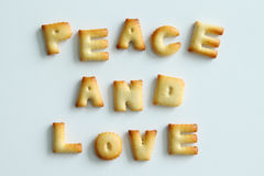 Inscription from the cookies on the white background. Text – Peace and love. Stock Photos