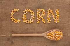 Inscription corn with a wooden spoon on burlap Royalty Free Stock Images