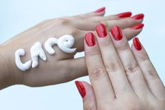 Inscription from cream care on the hand of women with red manicure on a pastel blue background. Female hand care. royalty free stock photo