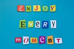 Inscription from cut letters - enjoy every moment on blue background. A word writing text showing enjoy every moment. Concept posi royalty free stock photos